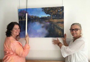 1603 Ro Burns and Christine McMillan hang artworks in Forbes